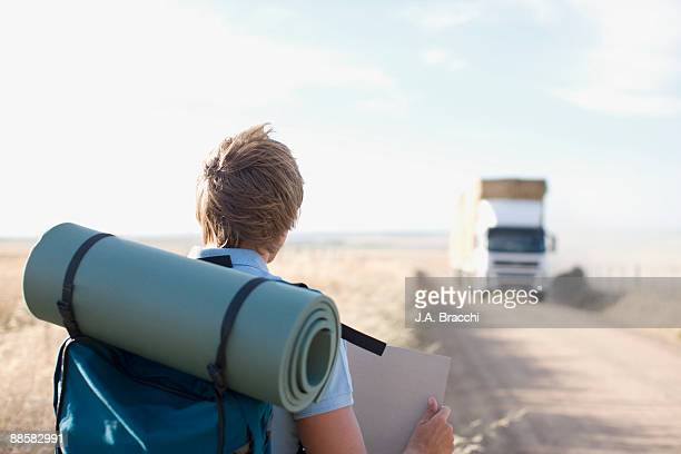 Backpacker hitchhiking along country road