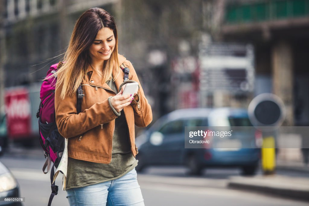 Backpacker in the city using phone : Stock Photo