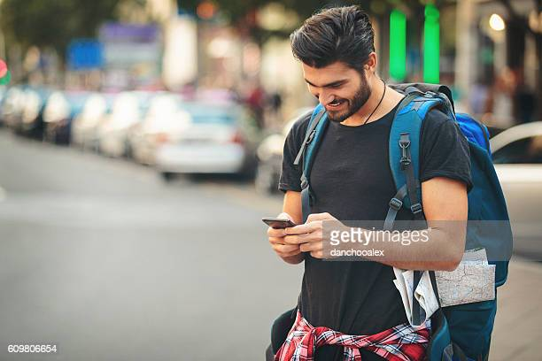 Backpacker in the city using smart phone