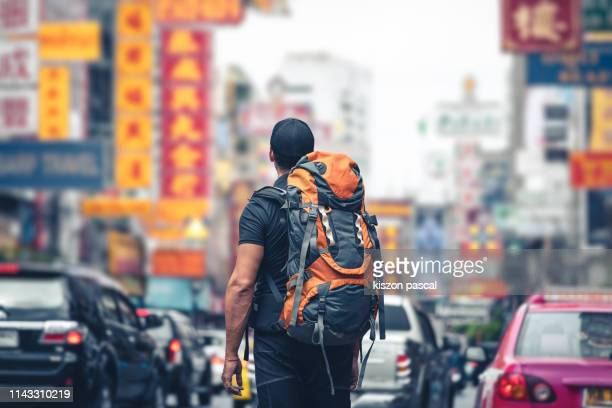 backpacker looking at the street in the chinatown of bangkok in thailand during day . - rucksacktourist stock-fotos und bilder