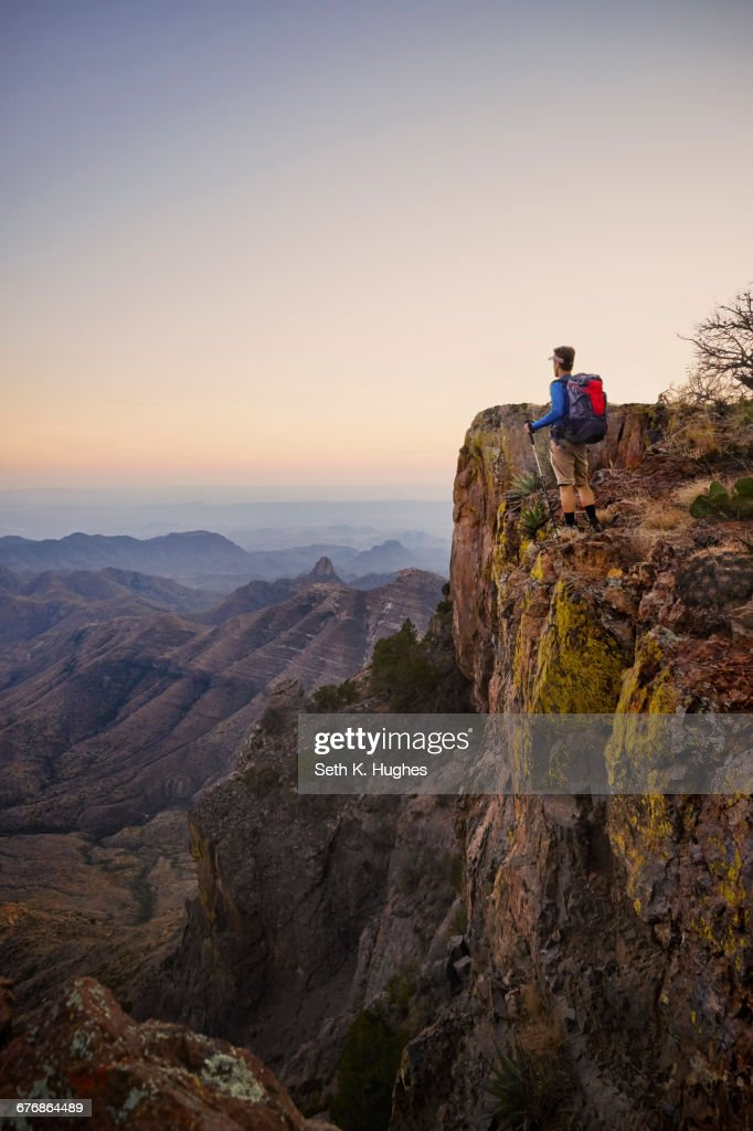 Backpacker looking out from ridge at dusk, Big Bend National Park, Texas, USA : Stock Photo
