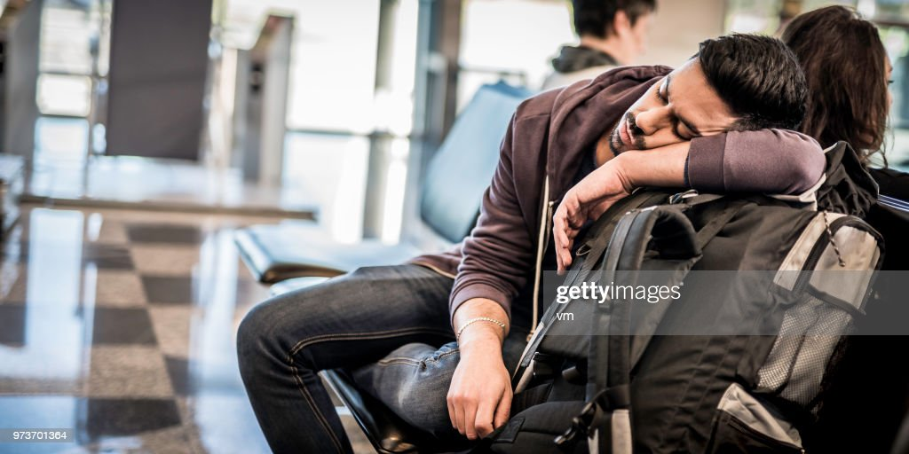 Backpacker napping while waiting for the airplane : Stock Photo