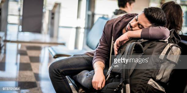 backpacker napping while waiting for the airplane - commercial aircraft stock photos and pictures
