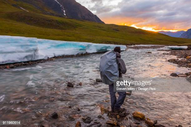 a backpacker observes the midnight sun peeking through the clouds from an unnamed fork of the atigun river still partially covered in aufeis (sheet-like ice formations) in a remote valley of the brooks range - miley fotografías e imágenes de stock