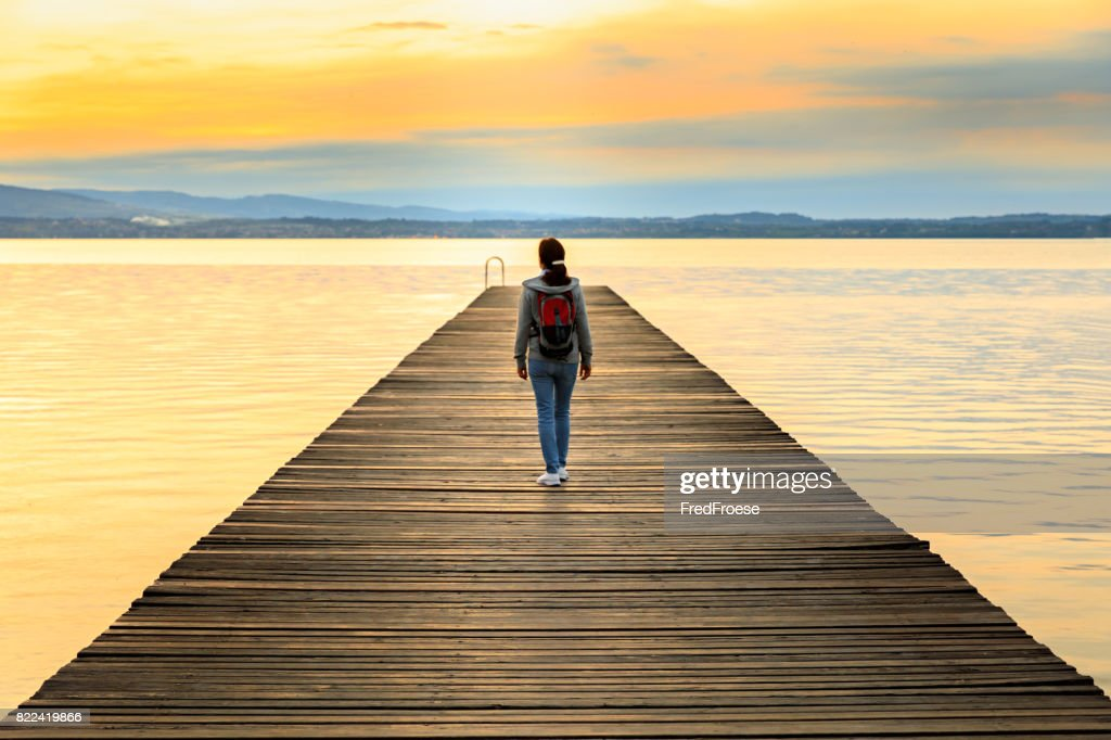 Backpacker on wooden jetty : Stock Photo
