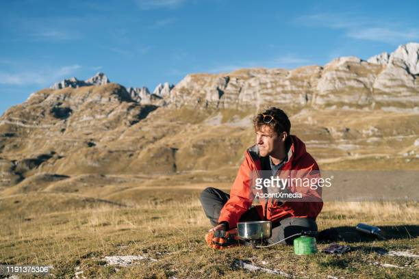 backpacker prepares meal on camp stove in mountains - wilderness stock pictures, royalty-free photos & images