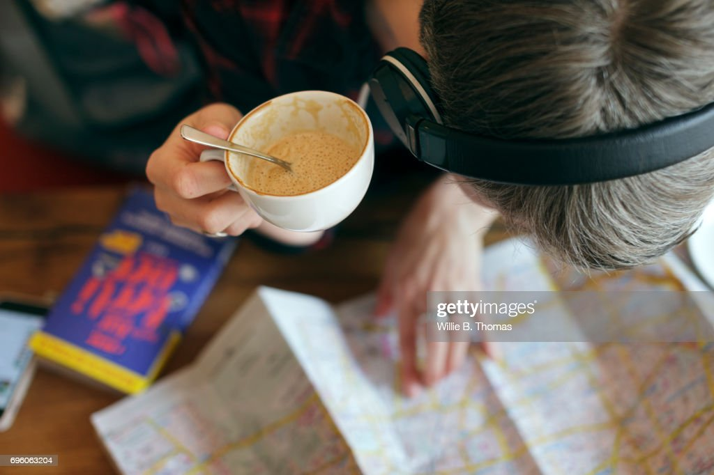 A Backpacker Reviews Her Route Whilst Sitting In A Cafe : Stock Photo