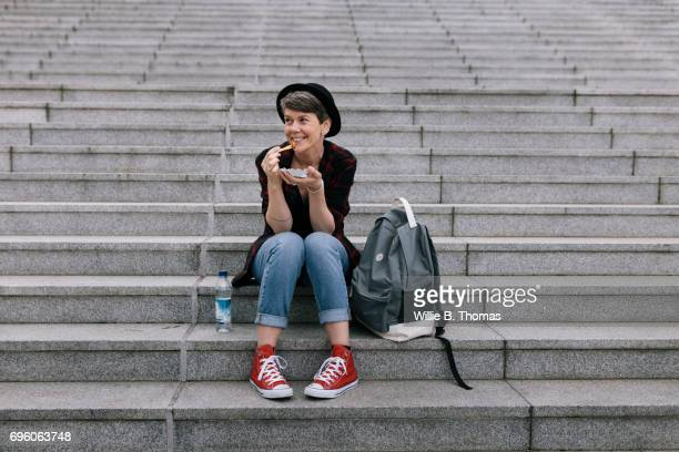 backpacker sits down on steps for a quick snack - hipster person stock-fotos und bilder