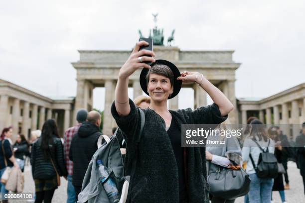 Backpacker Smiling And Taking Selfie At Tourist Attraction