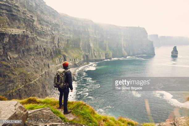 backpacker standing at the edge of the cliffs of moher, galway, ireland - ireland stock pictures, royalty-free photos & images