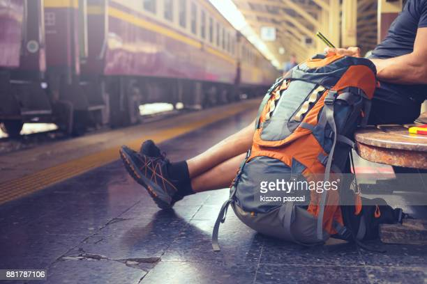 backpacker use phone in railway station while waiting train . . - rucksacktourist stock-fotos und bilder