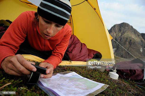 Backpacker uses GPS and map in Chugach State Park near Anchorage, Alaska.