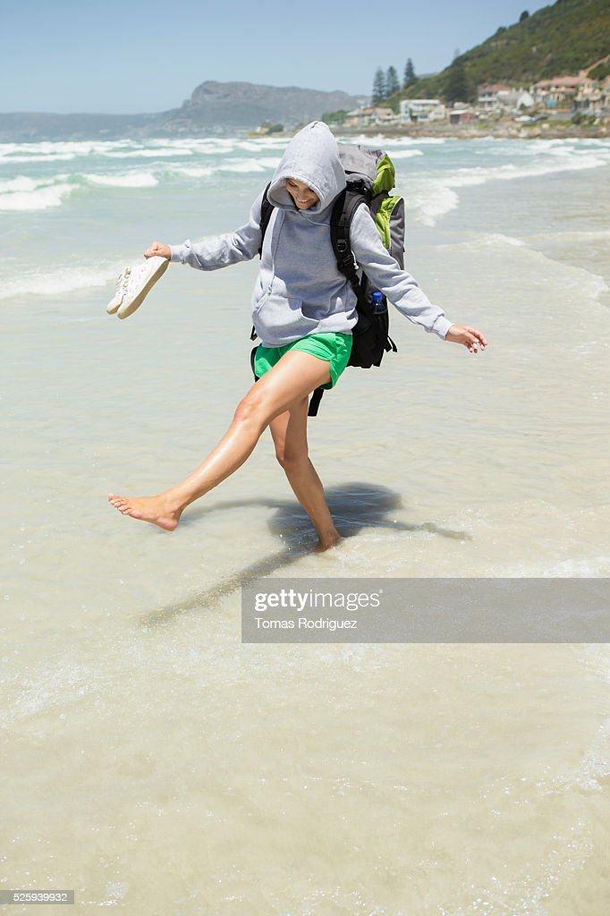Backpacker wading in sea : Foto de stock