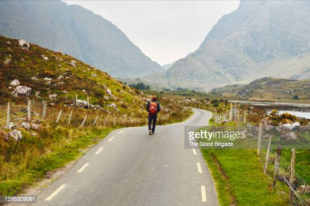 backpacker walking down empty road in killarney, ireland - discovery stock pictures, royalty-free photos & images