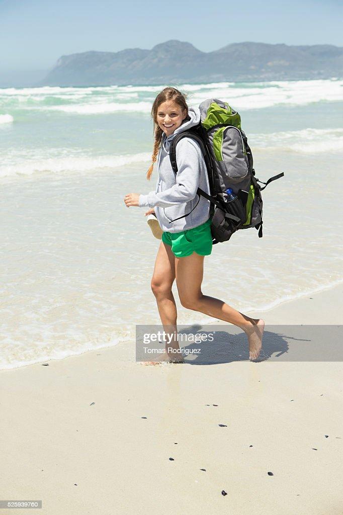 Backpacker walking on beach : Stock Photo