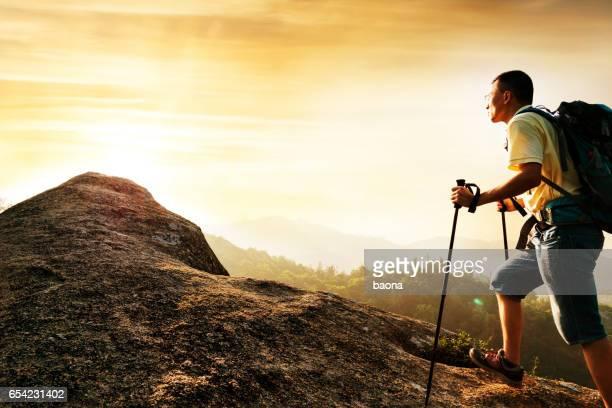 Backpacker walking on mountain peak
