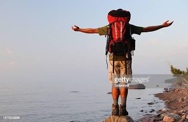 mochilero con brazos outstretch en rocky shoreline - parque estatal de porcupine mountains wilderness fotografías e imágenes de stock