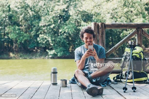 Routard avec téléphone intelligent reposant près d'un lac