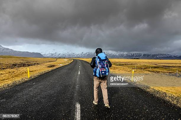 Backpacker with walking on the road in Iceland