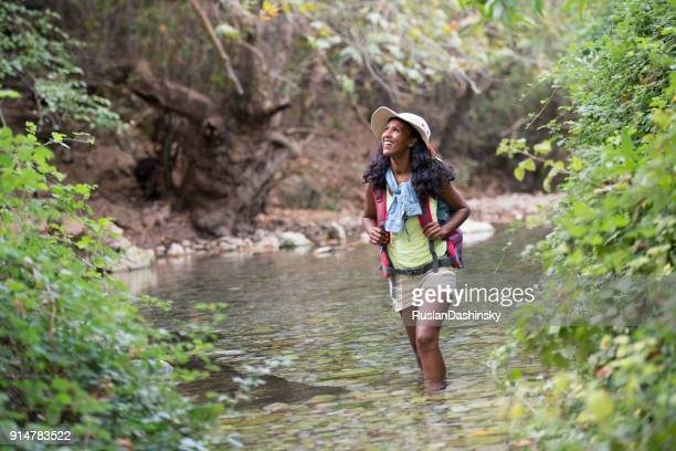Backpacker woman  wading in river in the forest.