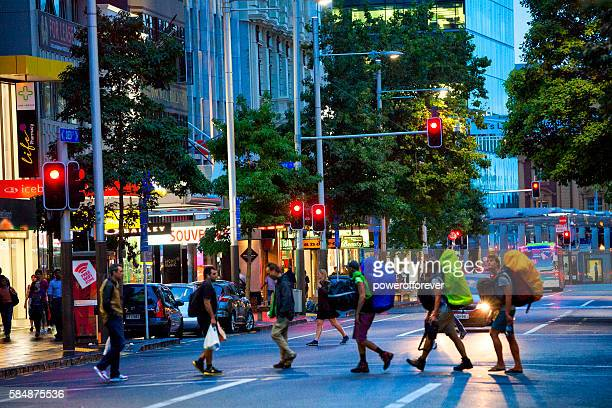 Backpackers crossing Queen street in downtown Auckland, New Zealand