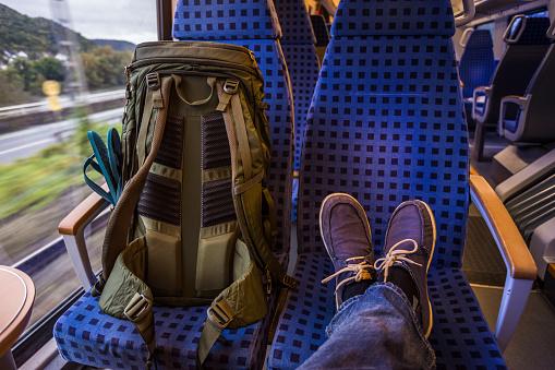 Backpacker's feet resting on seat in train - gettyimageskorea