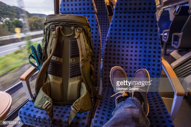 backpacker's feet resting on seat in train - seat stock pictures, royalty-free photos & images
