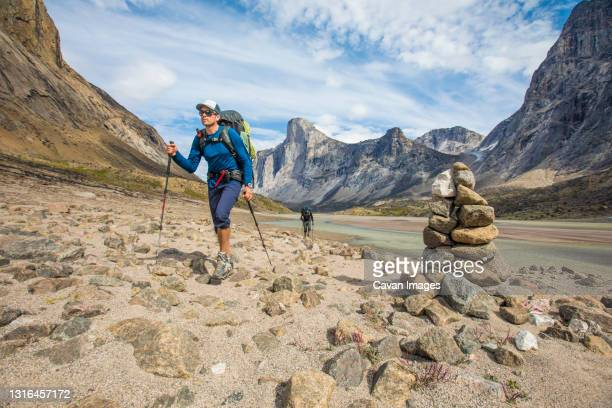 backpackers hike past cairn, marking the trail / route. - トレイル表示 ストックフォトと画像