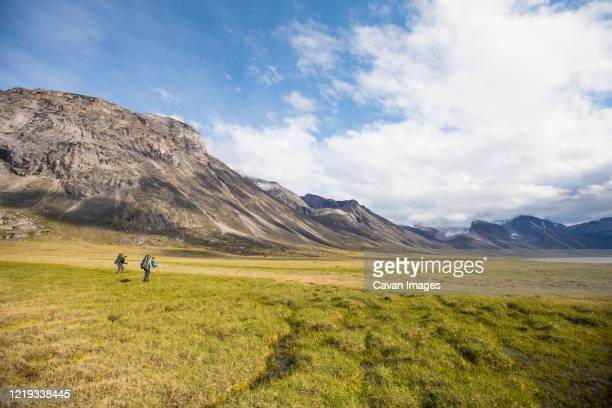 backpackers hiking in akshayak pass, auyuittuq national park. - baffin island stock pictures, royalty-free photos & images