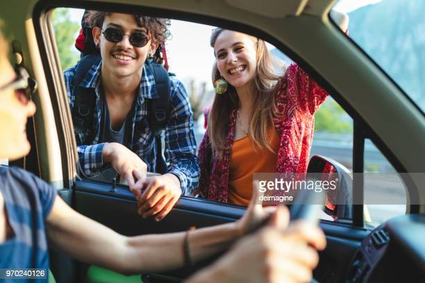 backpackers hitchhiking on the road - hitchhiking stock pictures, royalty-free photos & images