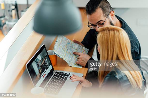 Backpackers Looking For Apartment On Their Laptop.
