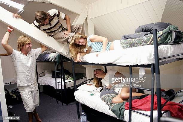 Backpackers relaxing in hostel dormitory.