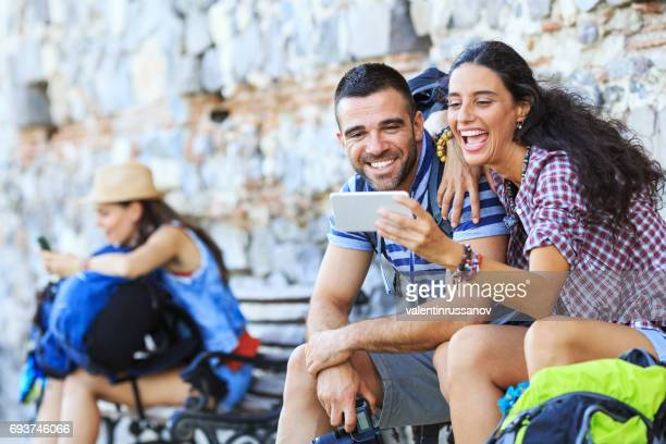 Backpackers resting on a bench and taking selfie