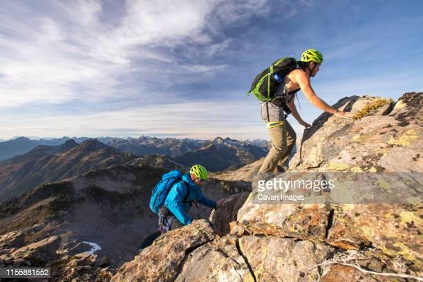 backpackers scramble up douglas peak, british columbia. - スクランブリング ストックフォトと画像
