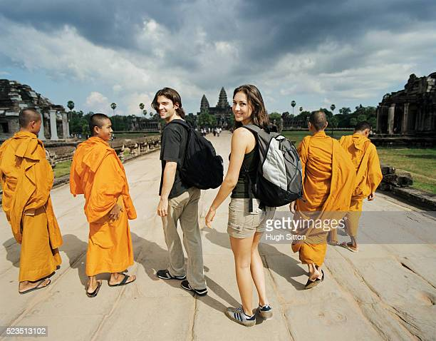 Backpackers Walking with Monks at Temple
