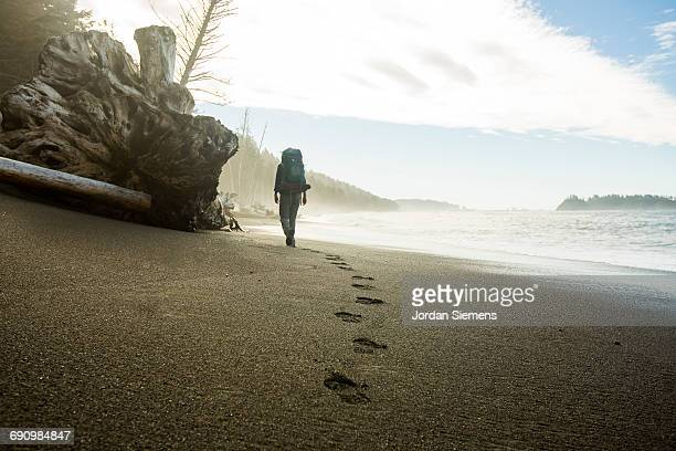 backpacking along a beach - pisada fotografías e imágenes de stock