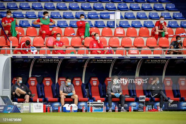 Backroom staff and substitute players of 1 FC Heidenheim sit with distance in the stands and on the bench during the Second Bundesliga match between...