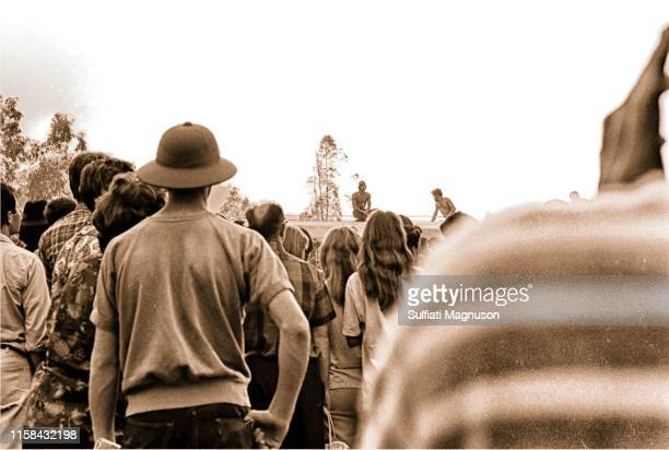 Backs of the crowd watching bare-chested men sitting on the top of the historic train car, one man in a pith helmet at the 1st Elysian Park Love-In...