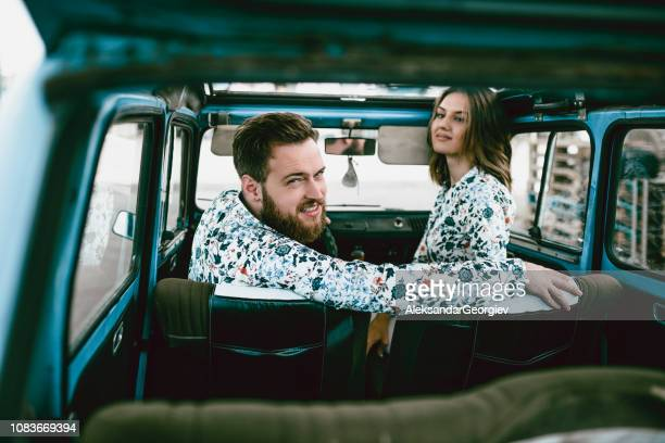 Backseat View Of a Cute Couple Travelling In Vintage Car