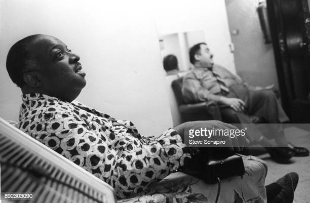 Backstage at the Apollo Theater American Jazz musician and bandleader Count Basie in a dressing gown sits with a telephone on the arm of his chair...