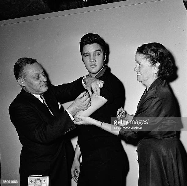 Backstage at the 'The Ed Sullivan Show,' American singer and musician Elvis Presley glances out of the corner of his eye at a smiling nurse while a...