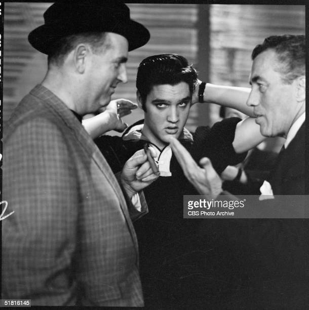 Backstage before his second appearance on the Ed Sullivan show American rock and roll singer and actor Elvis Presley adjusts his hair as Sullivan the...