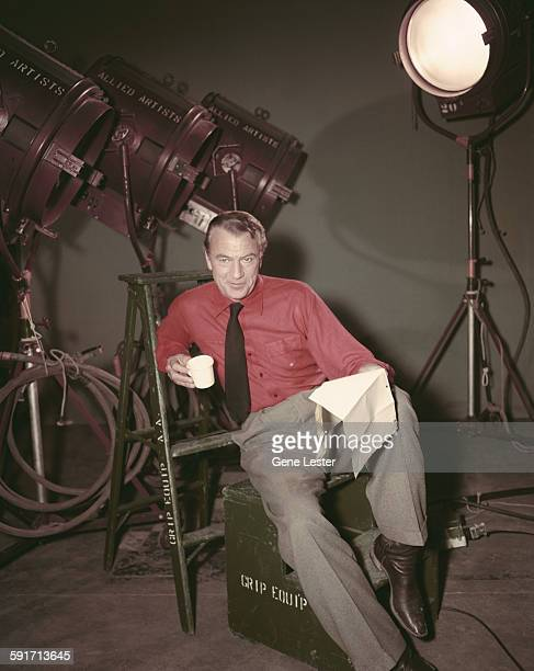 Backstage portrait of American actor Gary Cooper as he sits on an equipment box and leans back against a stepladder mid 1950s He wears a red oxford...