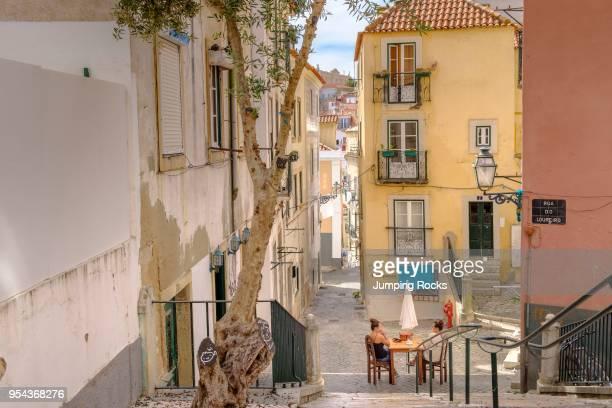 Backstreets of Alfama Neighborhood with woman relaxing Lisbon Portugal