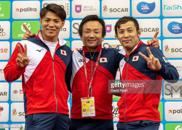 Backtoback world champions in 2017 and 2018 Hifumi Abe left and Naohisa Takato right stand with their coach Minoru Konegawa after the team event on...