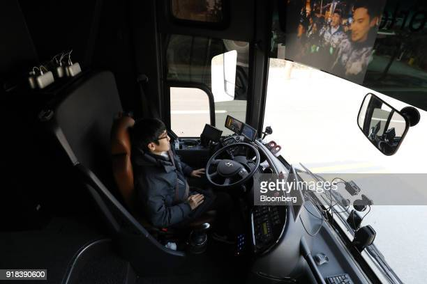 A backup driver sits onboard an autonomous 5G connected bus operated by KT Corp during a media event in Gangneung Gangwon Province South Korea on...