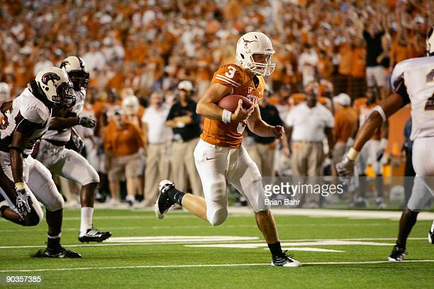 Backup quarterback Garrett Gilbert of the Texas Longhorns slips between the defense to score a touchdown against the Louisiana Monroe Warhawks in the...