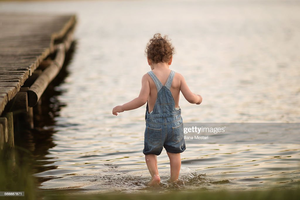 Backview of a boy in a lake : Stock Photo