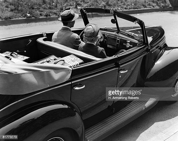 Backview Of A Man Driving A Sedan Convertible With Luggage In Back Seat Wearing Suit & Pork Pie Hat Blonde Woman Sitting Beside Him Top Down Touring.