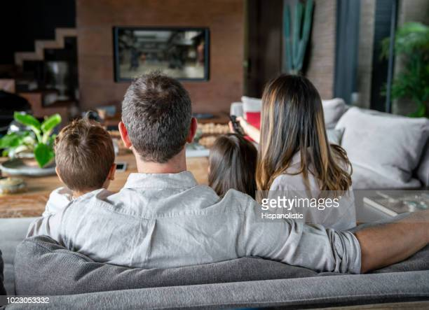 backview of family at home watching tv while mom changes channels - family watching tv stock pictures, royalty-free photos & images